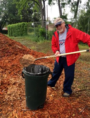 Man Shoveling Mulch into Trash Can at Free Mulch Day